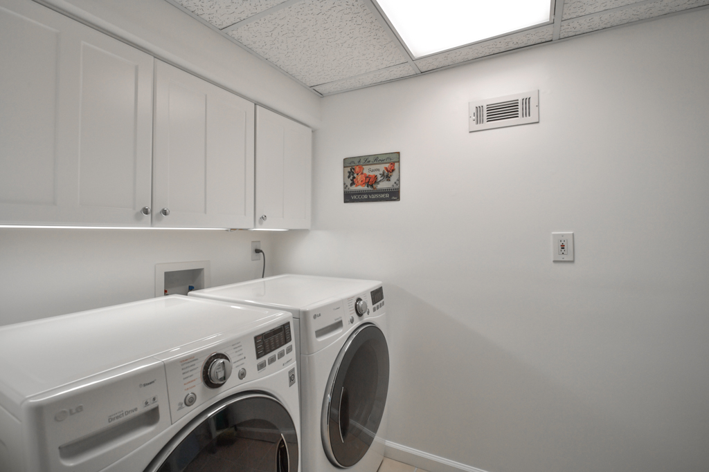 Laundry room includes a utility sink and lots of additional storage on this level